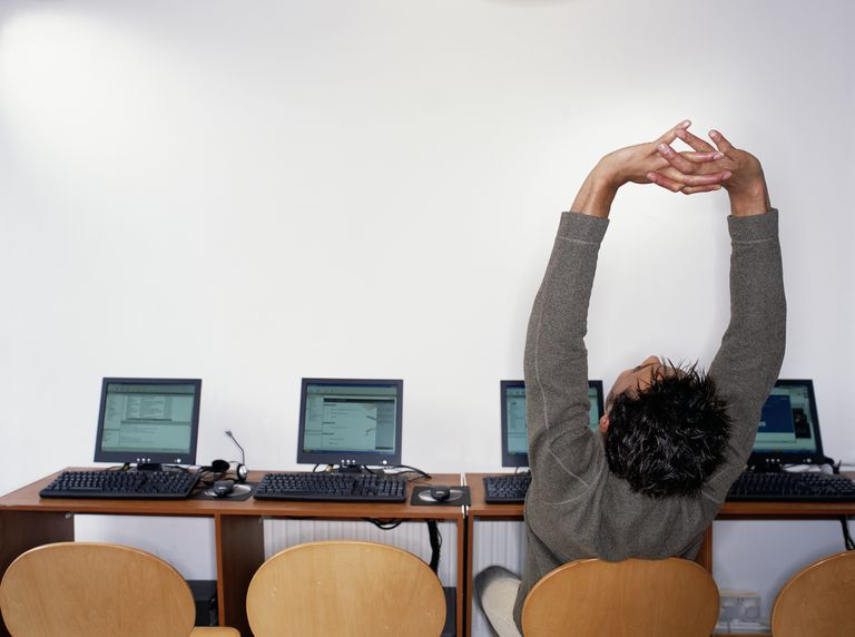 Man stretching his spine while sitting at his computer.