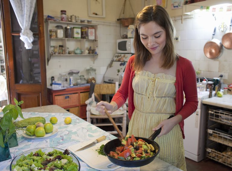 young woman holding a pan with sautéed vegetables