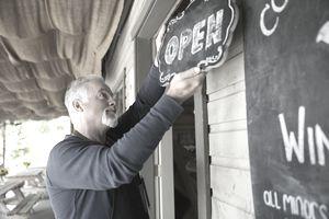 Senior male vintner hanging open sign at winery tasting room