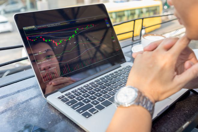 Man looking at stocks on laptop