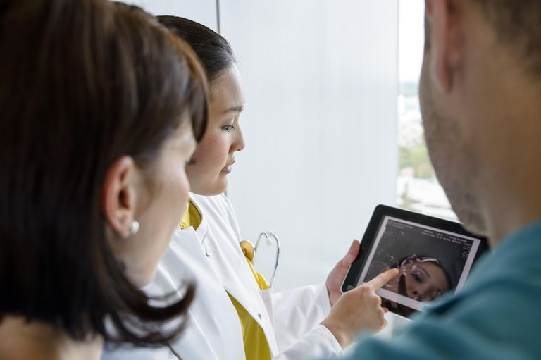 Female doctor using digital tablet with couple to explain blocked fallopian tubes
