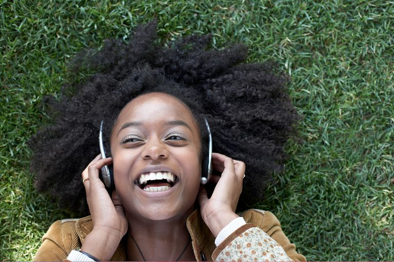 Woman listening to music lying on grass