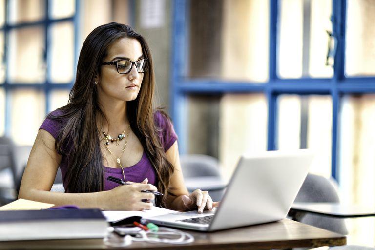 Happy Hispanic female student using laptop computer in classroom
