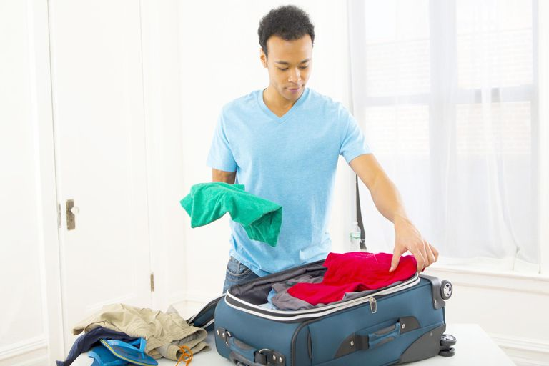 Mixed race man packing suitcase