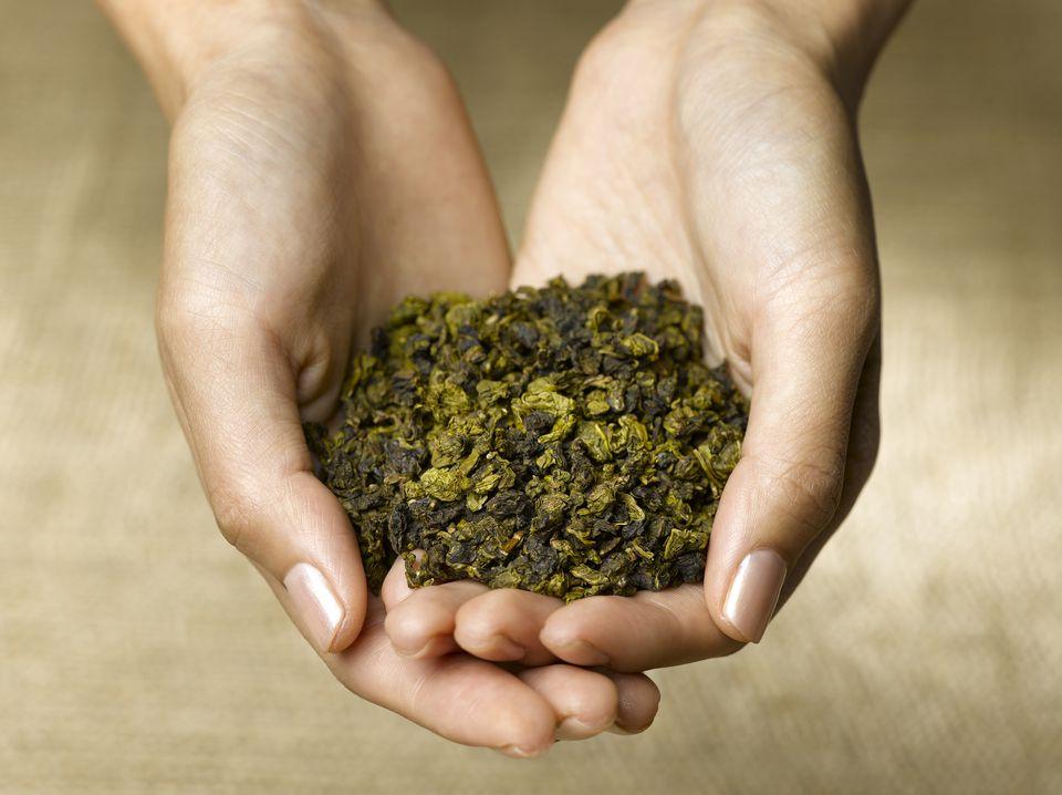 woman holding green tea leaves