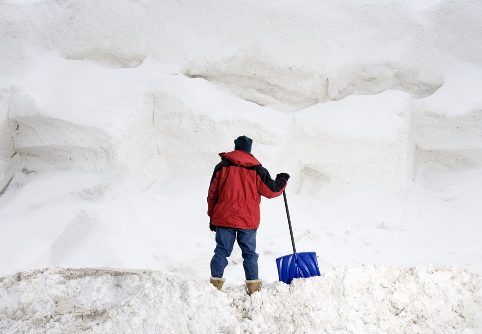 Man with shovel staring at big pile of snow.