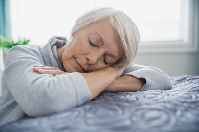 Tired woman with Parkinson disease laying on bed with eyes closed