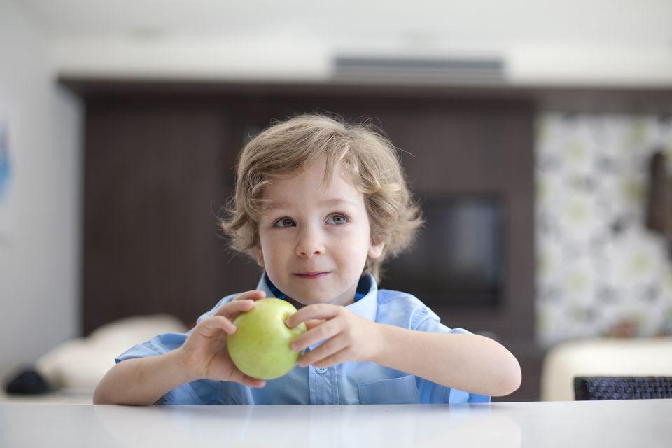 boy holding green apple