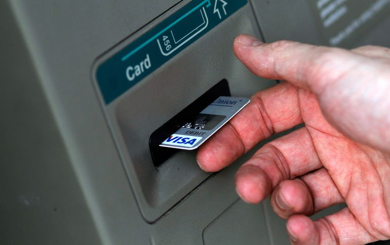 Man withdrawing money from ATM for retirement.