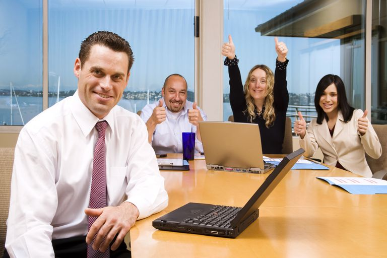 Thumbs up at the conference table by two women and a man