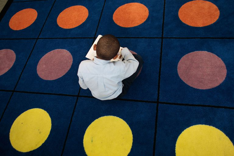 A student reads on a dotted carpet where students often sit for class