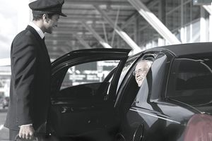 Chaffeur Holding the Car Door for a Happy Business Man