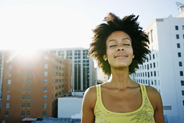 Mujer sonriendo con ojos cerrados coo meditando