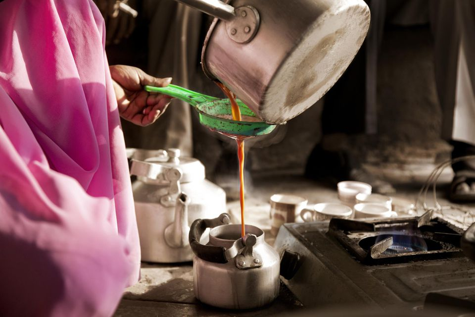 Pouring chai in kettle at stall