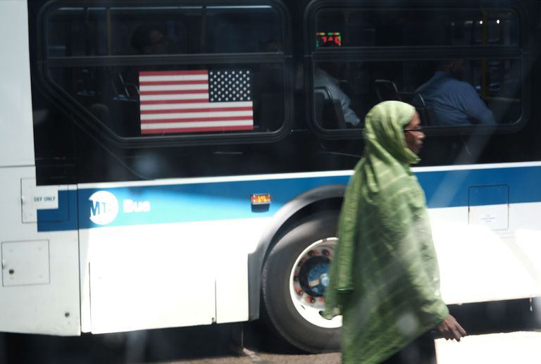 A Muslim woman walks in an ethnically a diverse neighborhood in Queens.