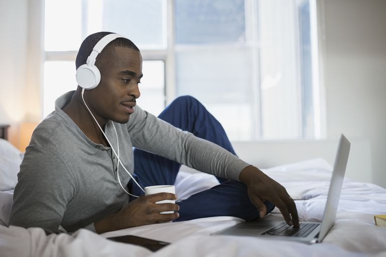 Man with headphones using laptop on bed