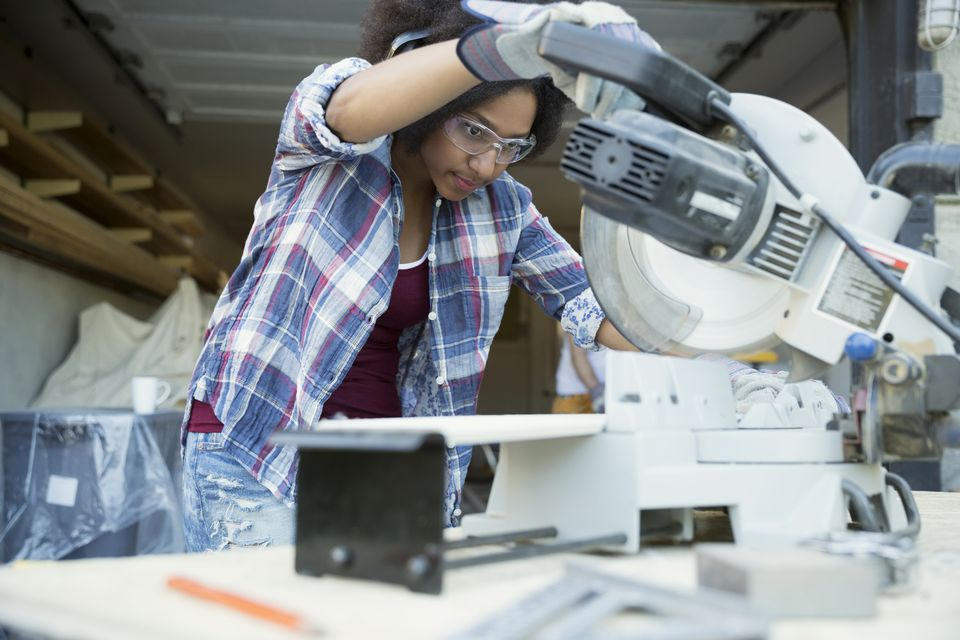 Woman working on table saw