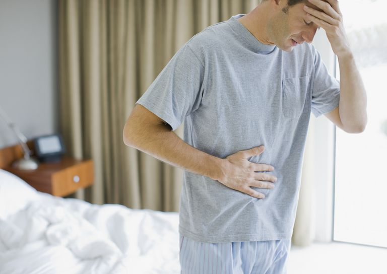 man in pajamas with stomach and headache
