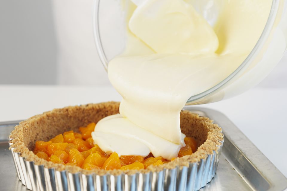 Pouring cheesecake mixture onto orange, close up