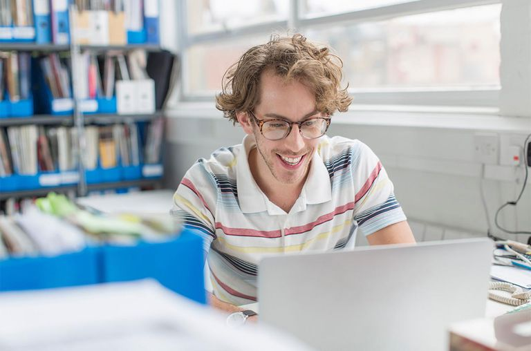 Young man using laptop and smiling in creative office