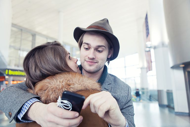 Young man texting on smartphone whilst hugging girlfriend in ferry terminal, New York, USA