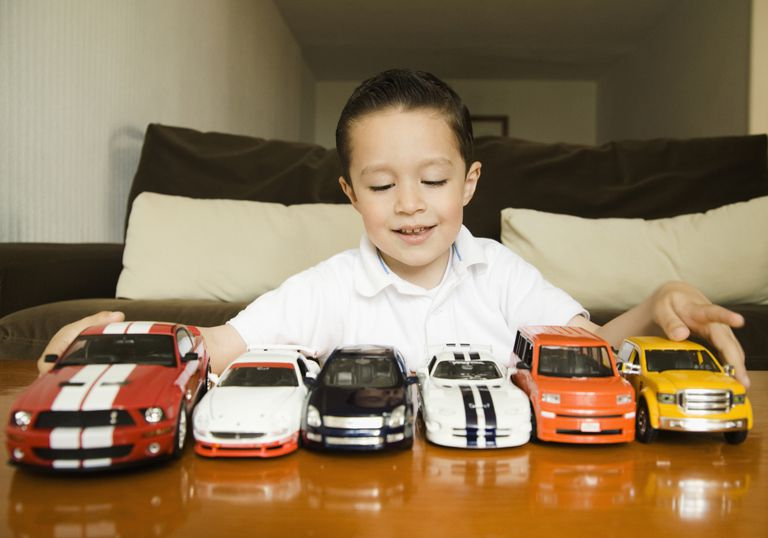 Boy lining up toy cars