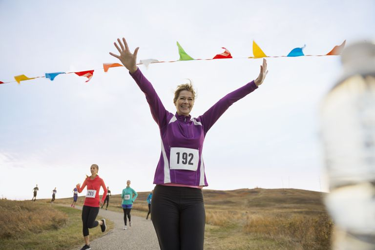female runner with arms outstretched at marathon finish line