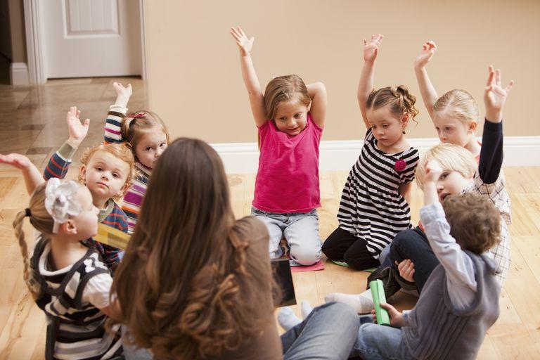 preschool class - children raising hands