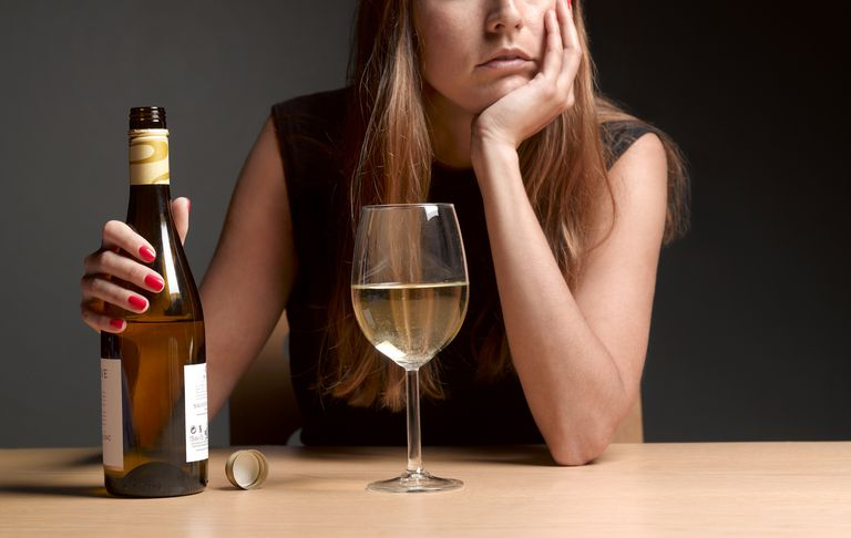 Sad woman drinking wine
