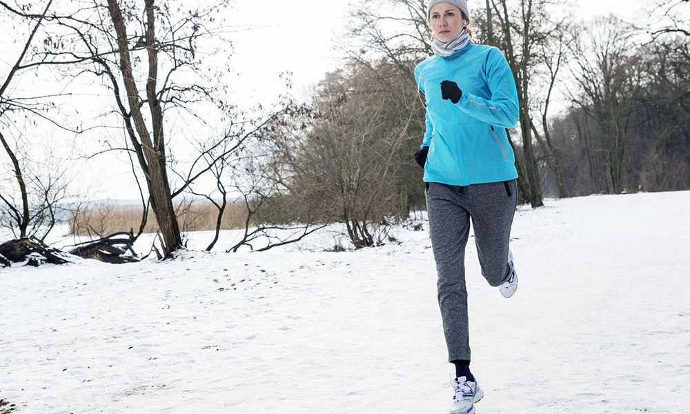 Young woman jogging in winter landscape