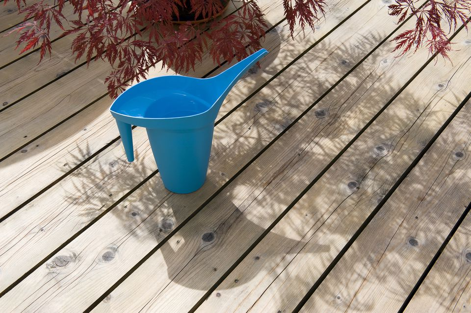 Unusual blue watering can on timber decking