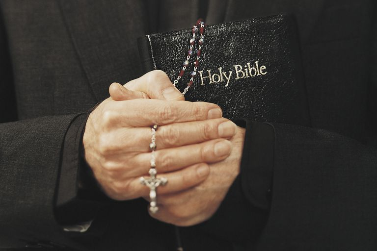 A Catholic priest holds a Bible and rosary in prayer. (Photo © Tom Le Goff/Getty Images)