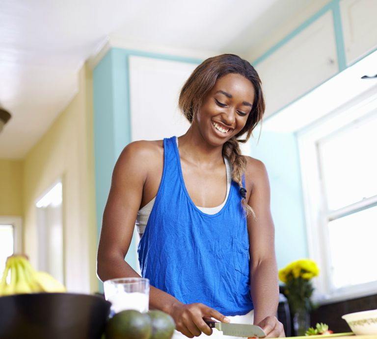 Young woman taking a training break, preparing food in kitchen