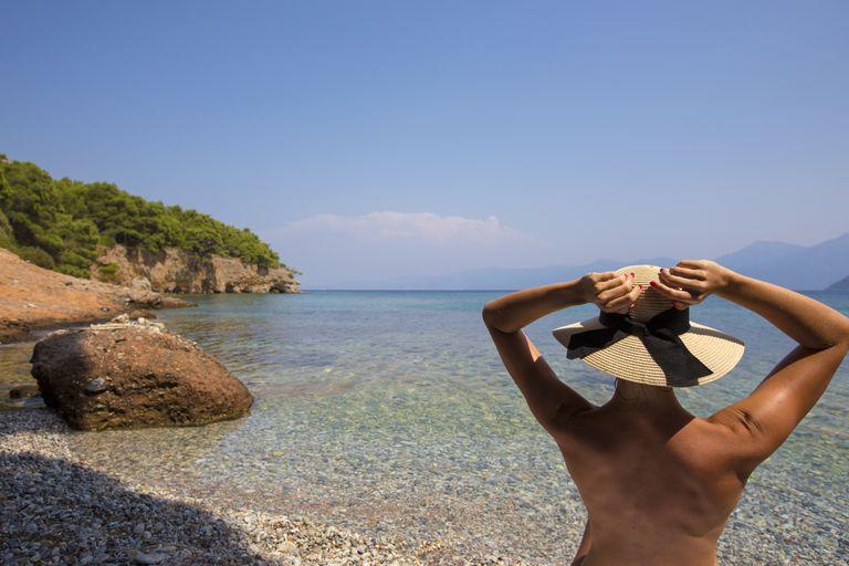 Una mujer disfruta la vista en una playa nudista.