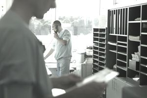 Man using telephone, male nurse in foreground