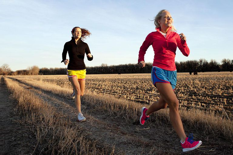 Two females jogging in the country.