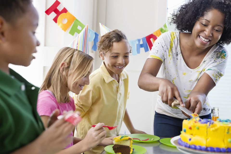 Happy young woman cutting birthday cake for children at party.