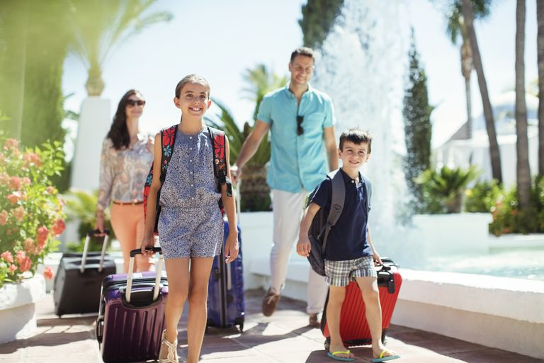 Family with suitcases passing by fountain in tourist resort