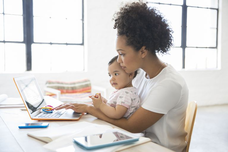 Mother working from home with daughter sitting on her lap