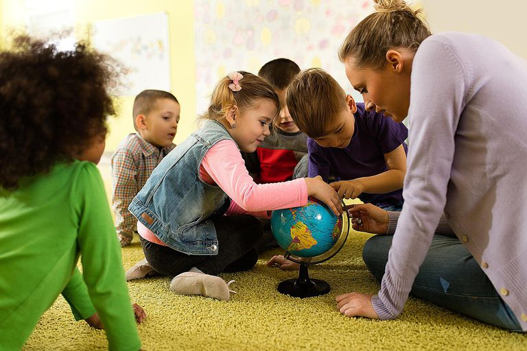 Kids at preschool using a globe to learn about geography.