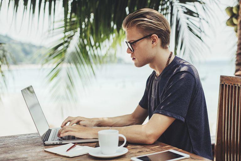 Caucasian man using laptop in cafe