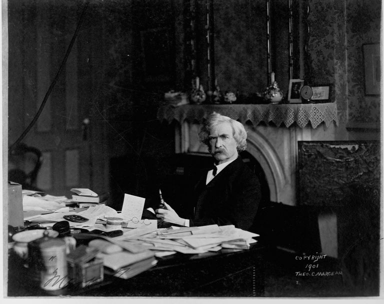 Mark Twain at a writing desk.