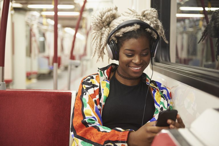 woman listening to cell phone with headphones on subway