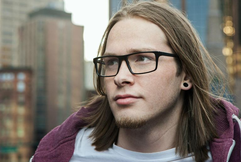 Teenager with long hair and glasses