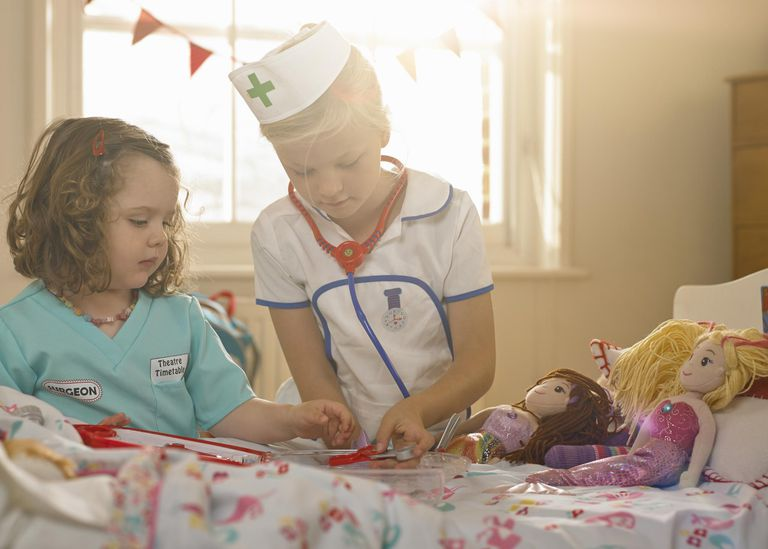 Two girls playing, dressed as doctor and nurse