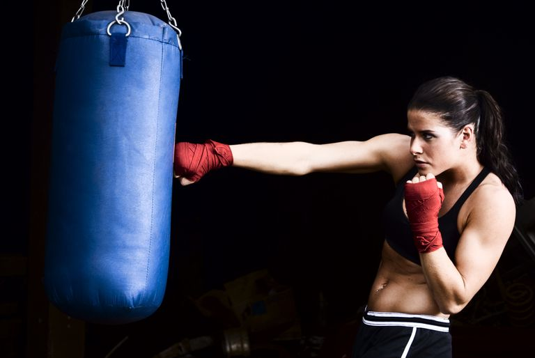 Photo of a woman hitting heavy bag.
