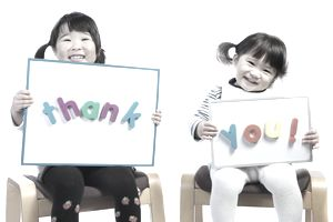 Two cute kids holding up sign that says thank you.