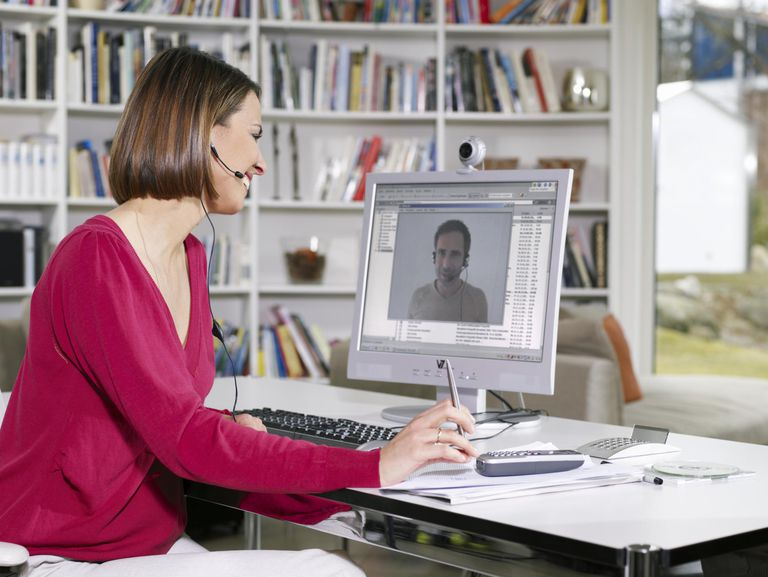 Woman Sitting Videoconferencing with Man on Computer