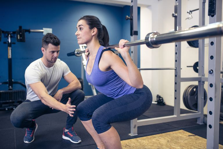 Woman with personal trainer working out in a gym. Coach is advising her what are the correct tecniques.