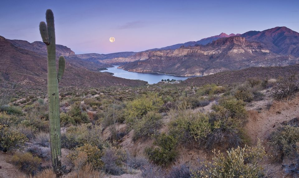 Moon setting down at sunrise over Apache Lake in Superstition Mountains, view from Apache Trail.